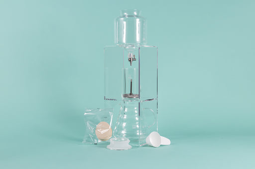 Tall clear acrylic tower stand with water reservoir and drip spout sitting over a glass cylinder with metal mesh filter for coffee grounds, with all glass coffee server with handle underneath and paper filter pack, server lid, and white plastic scoop on a teal background