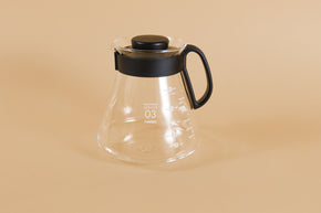 Glass coffee server with white text and level markings with closed black plastic handle and lid on an orange backdrop