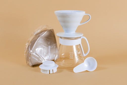 White cone shaped ceramic dripper with handle sitting on a glass server with white plastic handle next to pack of brown cone filters white plastic lid and scoop.