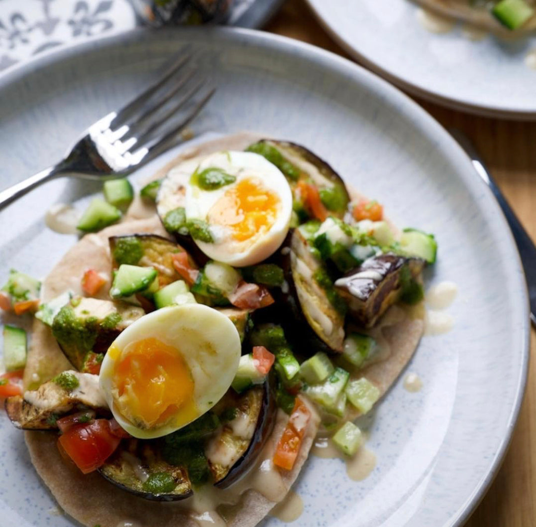 Roasted aubergine with boiled egg, tahini and herbed salad