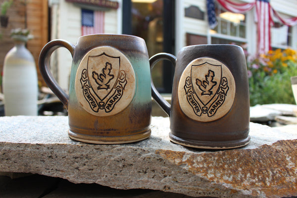 Two 12th Cavalry Regiment Bullet Coffee Mugs. One glazed in our Heirloom Glaze Scheme. The other glazed in our Java Glaze Scheme. Both are handmade in America by Potter's Fire, LLC. 12th Cavalry Regiment Insignia stained sepia and black.