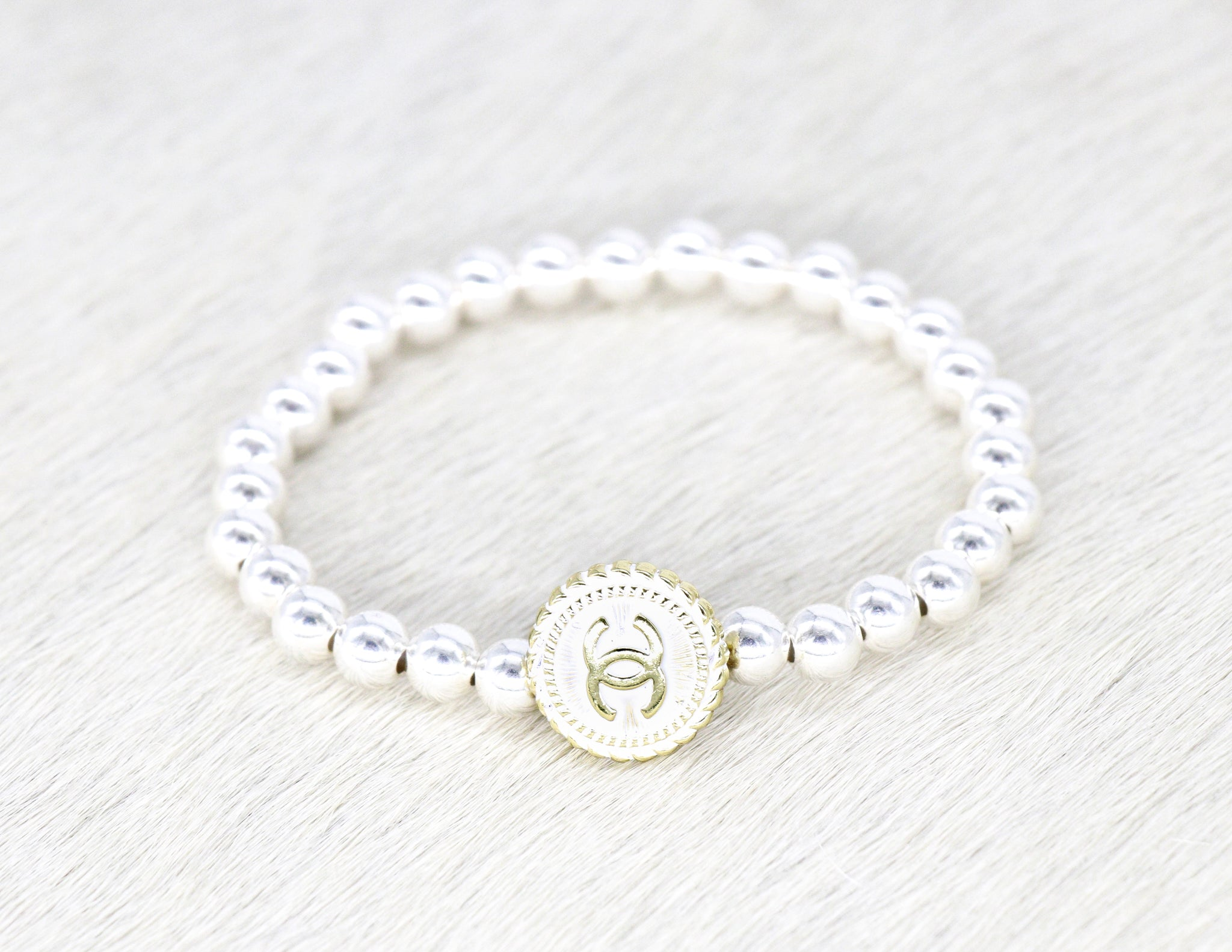 Sterling silver beads with a repurposed designer white and silver button bracelet