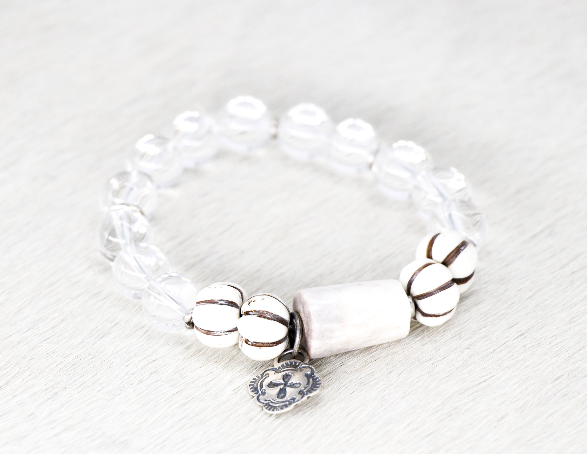 Crystal quartz bracelet with carved bone and a sterling silver cross pendant