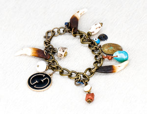 Charm bracelet with a repurposed designer pendant