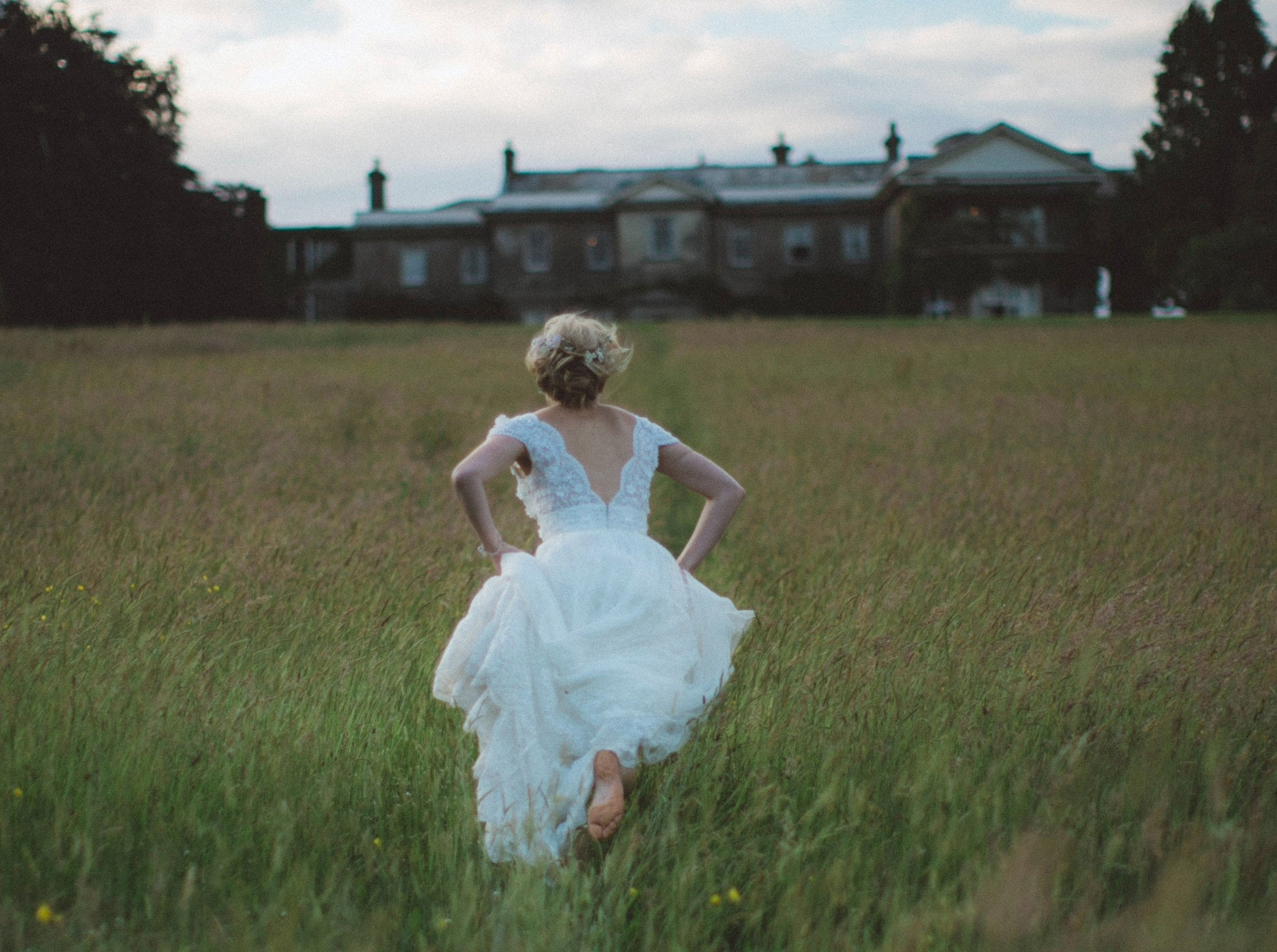 Woman in wedding dress runs through field towards large country house