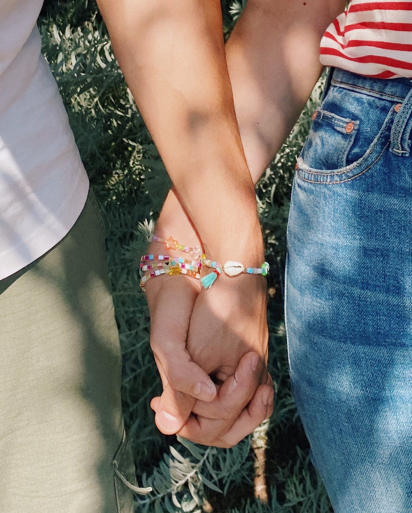Close up of two people holding hands wearing bracelets from the kits.