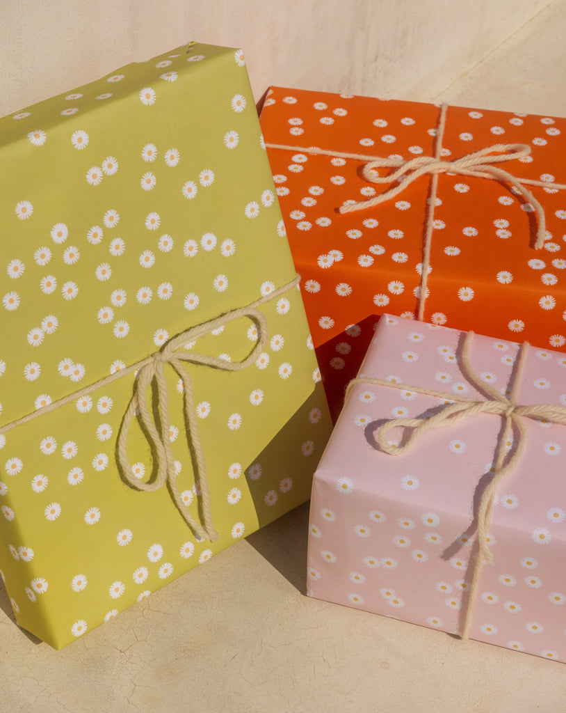 Three boxes wrapped in Adelfi 'Daisy Daisy Daisy' gift wrap, one pink, one orange, one green, all wrapped in white twine.