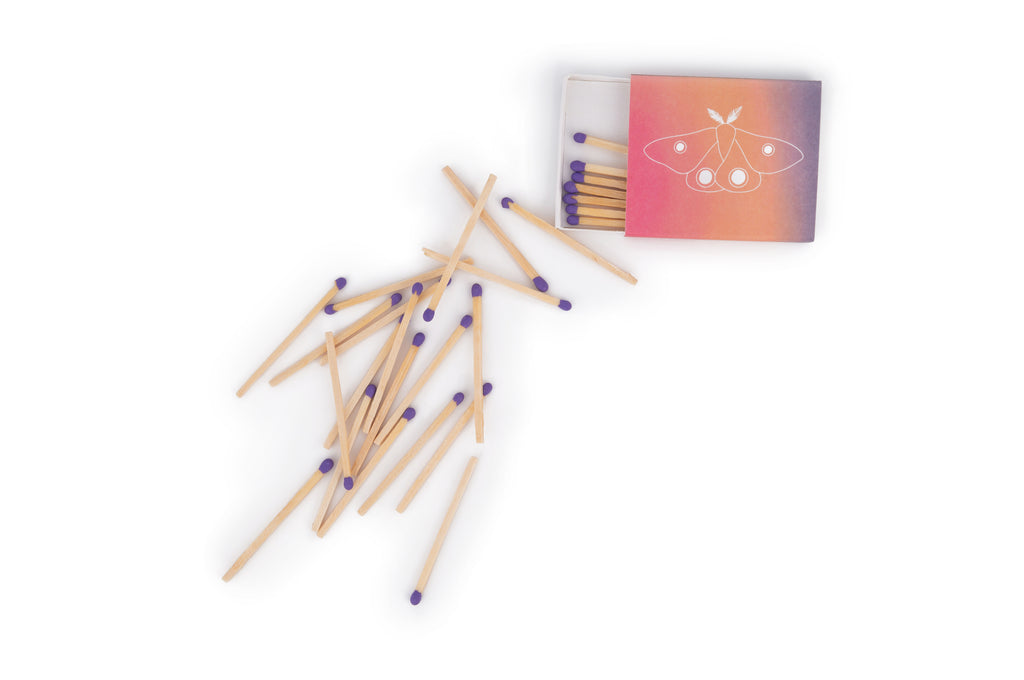 Adelfi matchbox open with purple matches spilling out