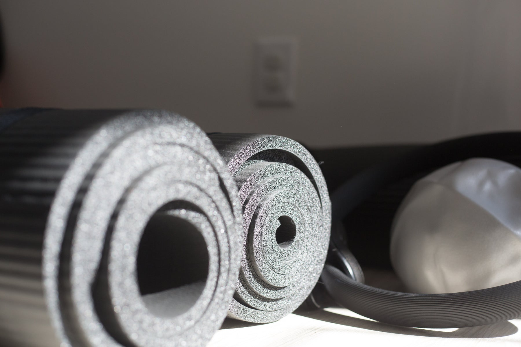 Close Up Photo of two black yoga mats next to a black Pilates Magic Circle and grey Pilates ball