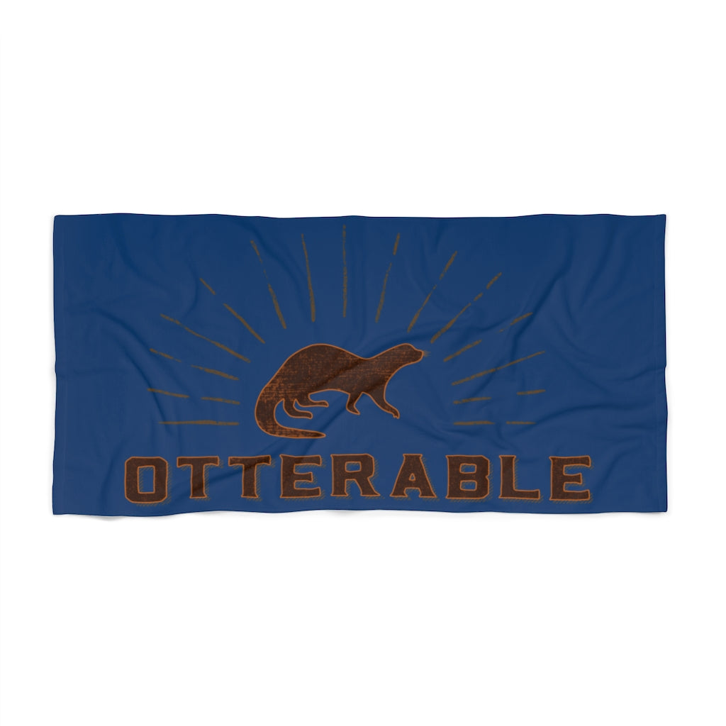 Blue beach towel with image of an otter and brown text otterable