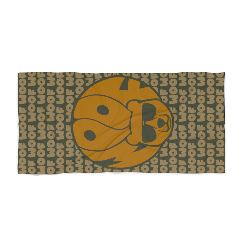 Green beach towel with light brown all over print woof and image of a bear head w woof as hair