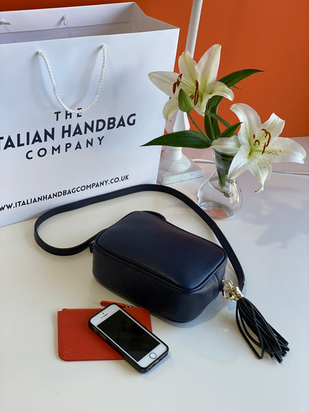 An image of a navy blue leather messenger bag with an orange purse and a mobile phone next to it. There is an Italian Handbag Company carrier bag in the background a vase of lilies.