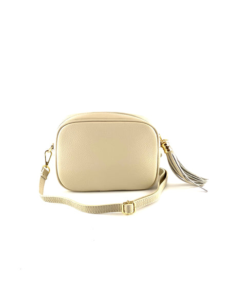 An image of a small cream leather messenger bag with a leather tassel on the zip which opens across the top of the bag.