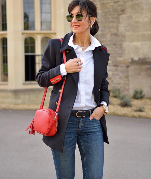 An image of a woman in a white shirt, navy blazer and jeans carrying a red leather messenger bag