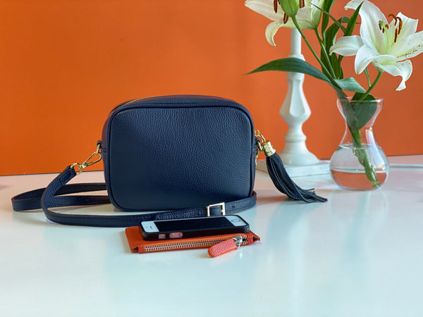 An image of a navy blue leather messenger bag with an orange purse and a mobile phone in front of it. There is a  vase of lilies next to the bag.