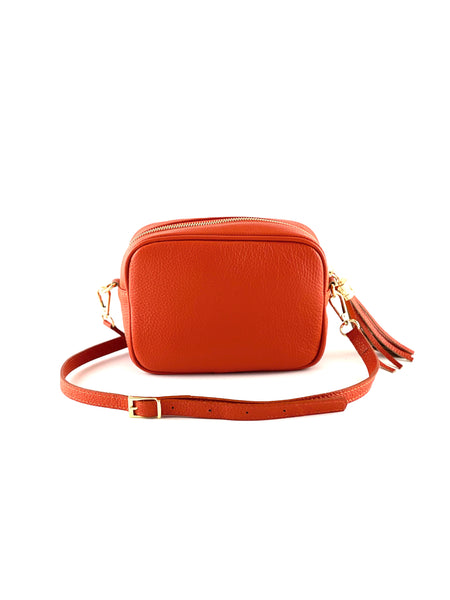 An image of a small orange leather messenger bag with a leather tassel on the zip which opens across the top of the bag.