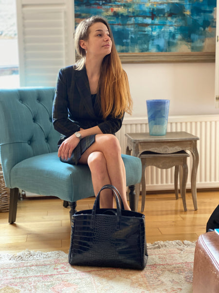 An image of a model sitting on a blue chair with the Natalia handbag on the floor in front of her.