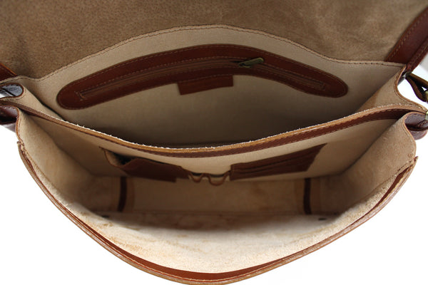 An image of the unlined interior of the Oscar shoulder bag showing a zipped pocket and some pen holder slots.