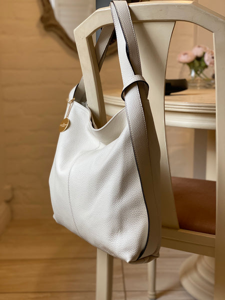 The cream Samona backpack/shoulder bag hanging on the back of a cahir.