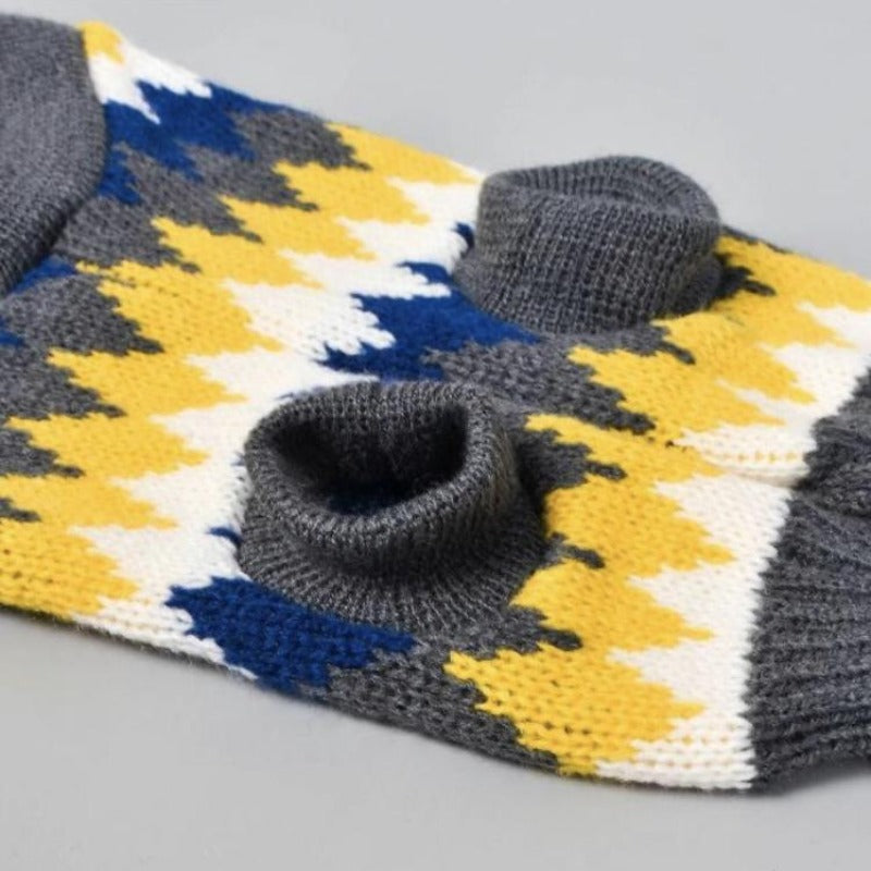 Stretchy dog sweater that has a pretty jagged multicolored design of gray, white, yellow, and blue alternately.