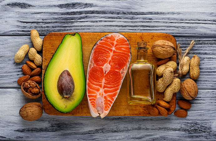 an avacado, salmon, oil, and various nuts displayed on a platter