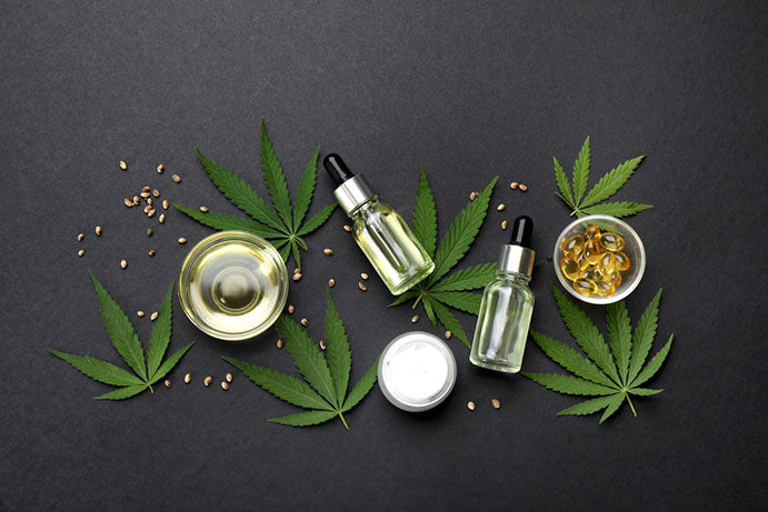 several cbd products displayed on top of hemp leaves and seeds