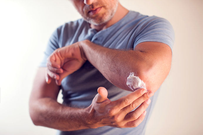 man putting cream on elbow joint