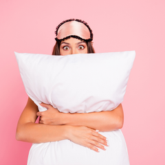 Picture of a woman with a pink sleep mask on her head clutching a pillow to her body.