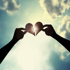 Picture of hearts holding up a broken heart with the background of a sun shining through the clouds.