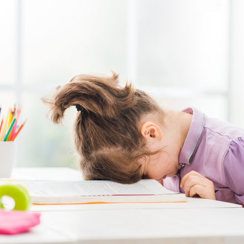 Home school not quite working out? Picture of small girl with forehead banged onto book