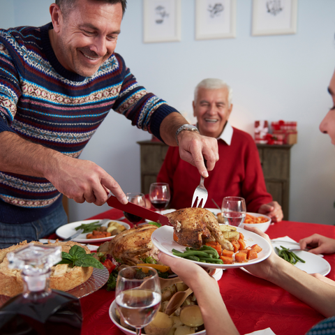 Man dishing up Christmas dinner with his family seated at the table