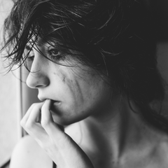 Black and white image of a woman crying with mascarra drunning down her face.  Her fingertips placed at her lips she is looking out of a window sadly.