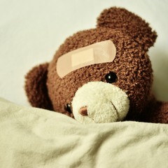 toy bear looking forlorn with a plaster on its head