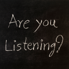 """A black bard with the words """"Are you listening ?"""" written in chalk"""