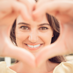 Picture of a woman looking through her hands shaped like a heart