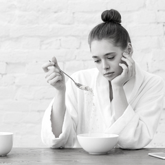 A woman seated with a fed up look on her face staring at her cereal as she tentatively pours the dry substance back into the bowl from her spoon.