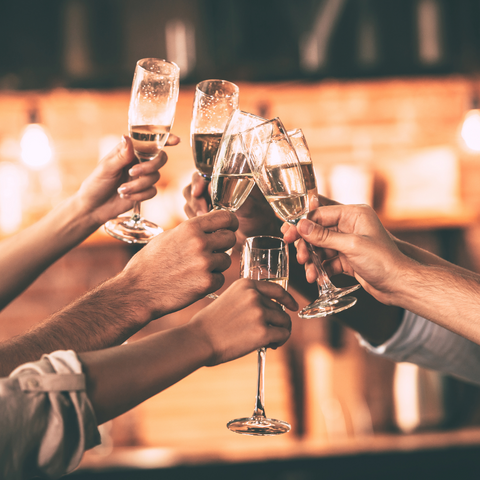 hands holding champagne glasses, placing the glasses together for cheers