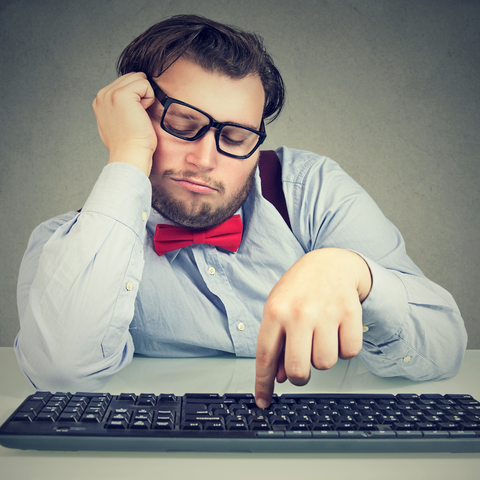 Man with glasses crooked on his face, looking bored resting his face on his hand and pressing one key on the keyboard in front of him