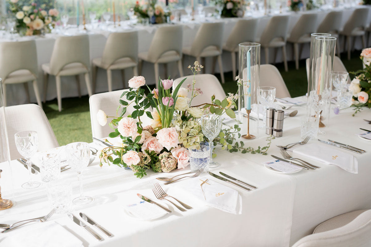 A dining table for a wedding with white table cloths, crystal rocks and champaign glasses and a table flower bouquet