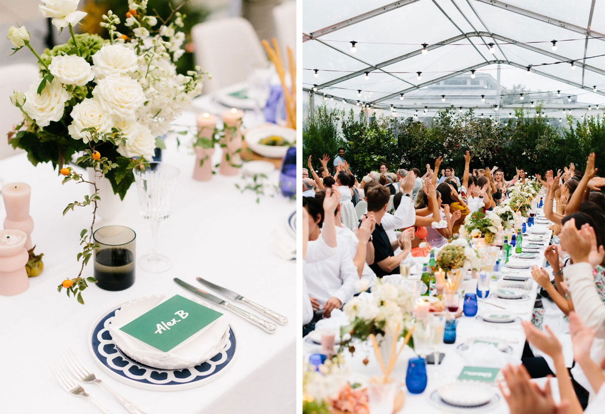 A wedding reception set up in a big tent with many people sitting at long tables and colourful flowers as decoration