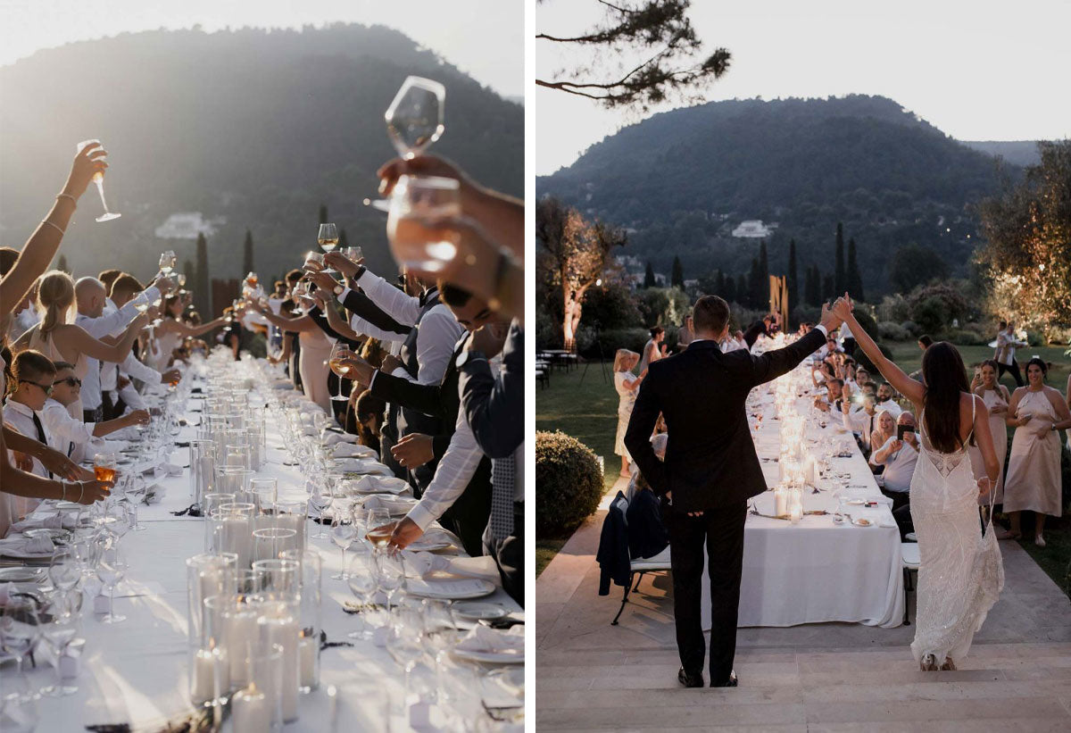 A wedding reception organised by After The Rock and set up outdoors with a long white table in the middle and guests sitting on each side of the table raising their glasses