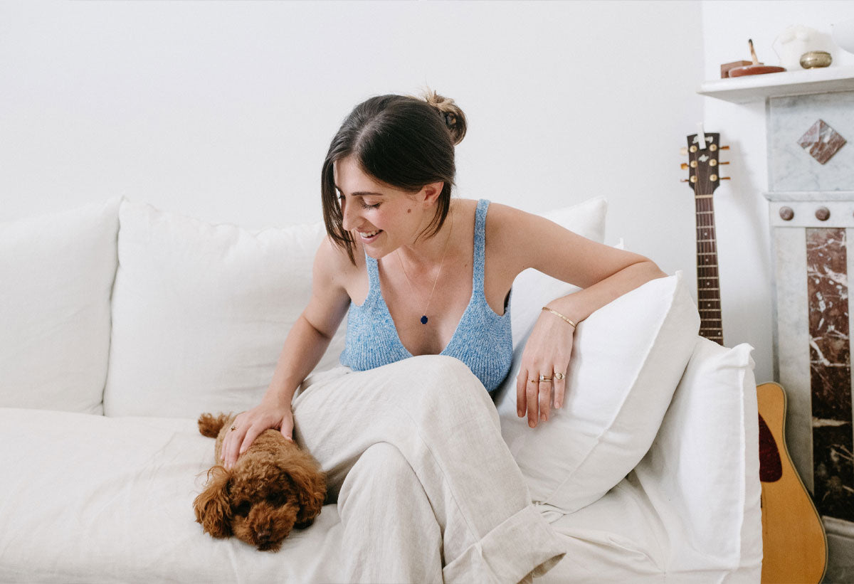 Amanda Bardas wearing a light blue top and sitting on a white couch while stroking her dog's head
