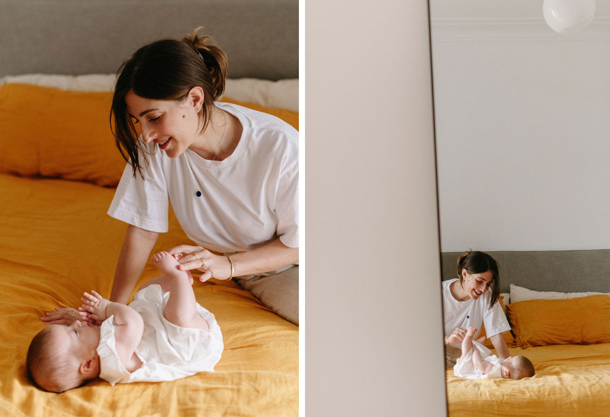 Amanda Bardas and her baby daughter smiling and sitting and lying on a bed with a yellow bed sheet