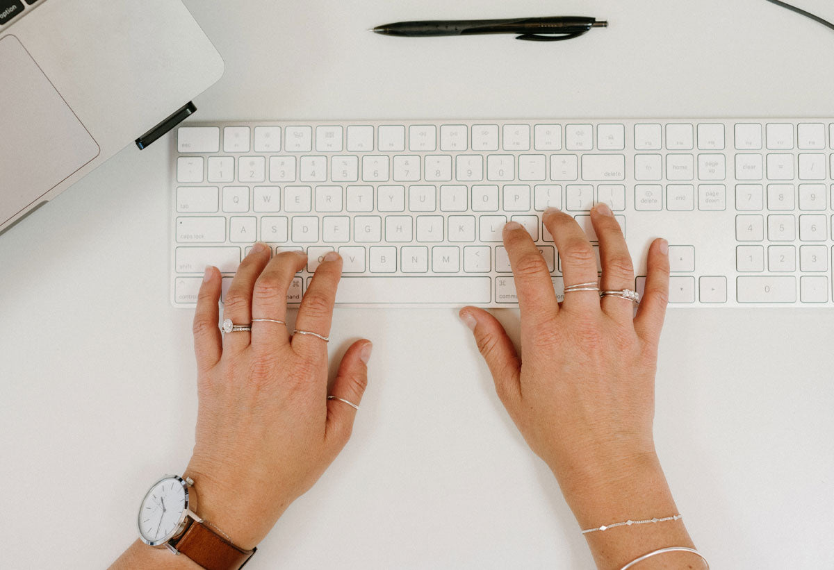 Kristen Sutherland's hands typing on a grey Mac keyboard wearing White Gold rings