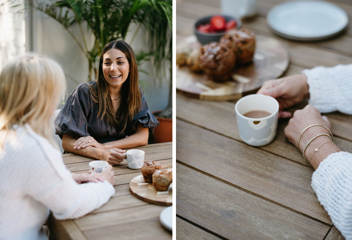 Zinovia and Julia sitting at a wooden table laughing and having tea and muffins