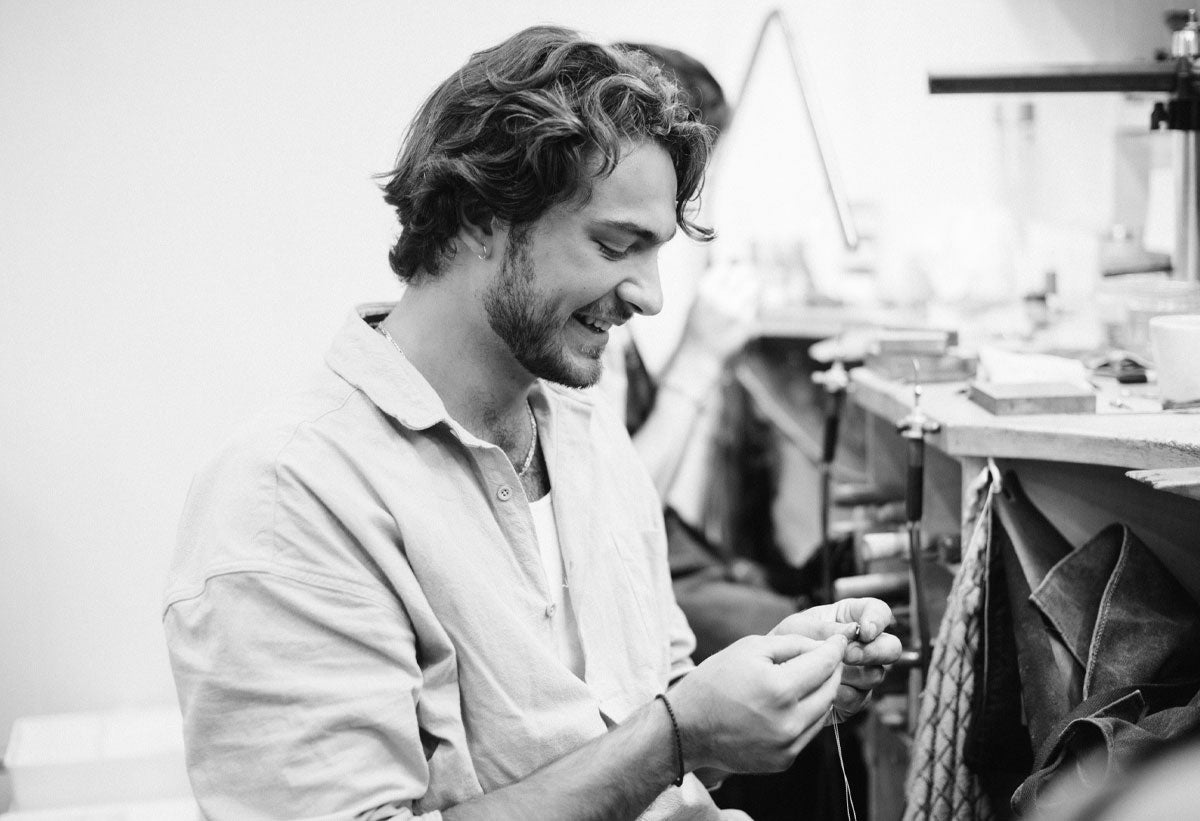 Dionysios Tsinonis sitting at his jewellery work station working on a necklace