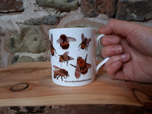 Load image into Gallery viewer, Bee mug by Alice Draws The Line. A china tea or coffee cup covered in bee illustrations