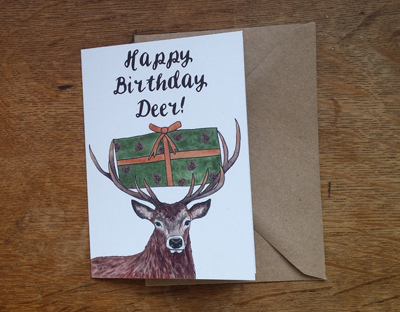 Happy Birthday Deer! Greeting Card. A Birthday stag carrying a birthday present in woodland colours in his antlers by Alice Draws The Line