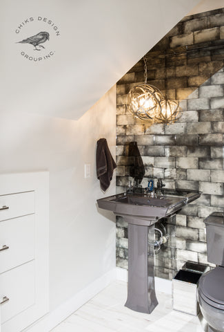 Image of antique mirror tile feature wall, chandelier and built in storage in powder room.