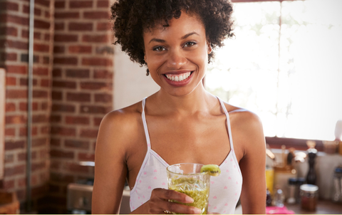 Smiling woman holding glass of banana bread overnight oats